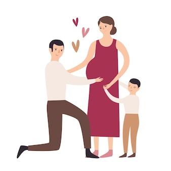 妊娠中の母親と父親を抱き締めて膝の上に立って彼女の腹に触れる息子