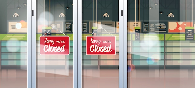 Sorry we are closed sign hanging outside grocery store with empty shelves coronavirus pandemic quarantine