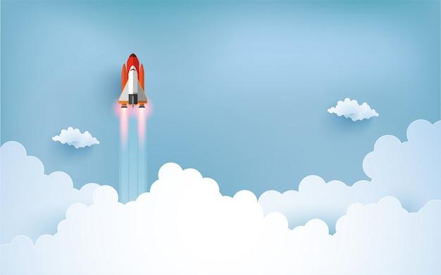 宇宙船のイラストが雲の上を飛んでいます。紙アートデザイン