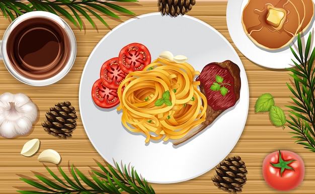 Spagetti and steak close up on desk background with some leaves props
