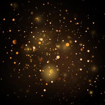 きらめく魔法の金黄色いダスト粒子。ボケ効果で抽象的な黒の背景。