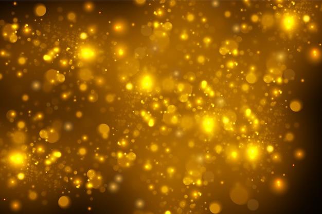きらめく魔法の金黄色のほこりの粒子。魔法の概念。ボケ効果のある抽象的な黒の背景。