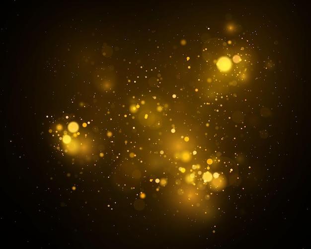 きらめく魔法の金黄色のほこりの粒子。魔法の黄金の概念。ボケ効果のある抽象的な黒の背景。