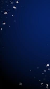 스파스 강설량 크리스마스 배경입니다. 짙은 파란색 배경에 미묘한 날아다니는 눈 조각과 별. 사랑스러운 겨울 은색 눈송이 오버레이 템플릿입니다. 추가 세로 그림입니다.
