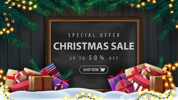 Special offer, christmas sale, up to 50% off, discount banner with wooden wall, christmas tree branches, garland, chalk board with offer and presents