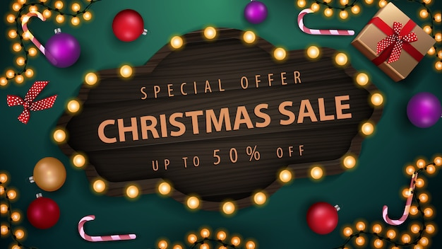 Special offer, christmas sale, up to 50% off, green discount banner with christmas balls, candy canes, garland and gifts, top view
