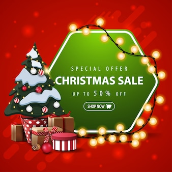 Special offer, christmas sale, up to 50% off, square red and green banner with hexagonal sign wrapped garland and christmas tree in a pot with gifts