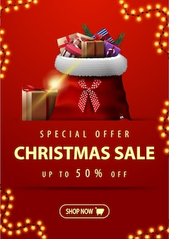 Special offer, christmas sale, up to 50% off, vertical red discount banner with garland, button and santa claus bag with presents