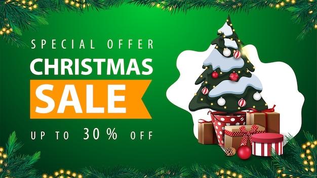 特別オファー、クリスマスセール、最大30%オフ、背景に抽象的な形の緑の割引ウェブバナー、花輪フレーム、クリスマスツリーの枝で作られたフレームとギフト付きのポットにクリスマスツリー