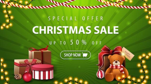 Специальное предложение, рождественская распродажа, скидка до 50, красивый зеленый баннер со скидкой с гирляндами, подарком и мишкой тедди.