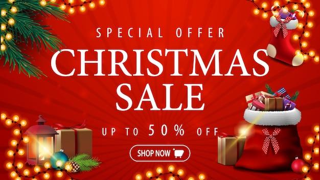 Специальное предложение, рождественская распродажа, скидка до 50%, красный баннер со скидкой с гирляндой, ветви елки, рождественский чулок и красная сумка санта-клауса с подарками