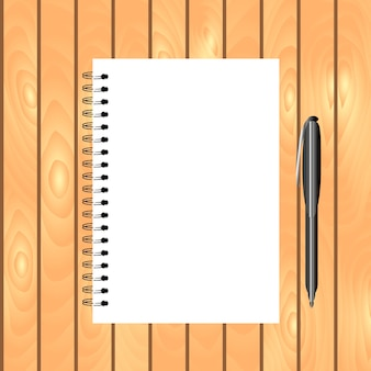 Spiral bound notebook with pen on the light wooden background