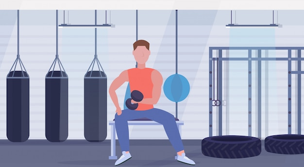 Sports man doing exercises with dumbbell muscular guy sitting on bench biceps workout concept training in gym with punching bags modern health club interior flat full length