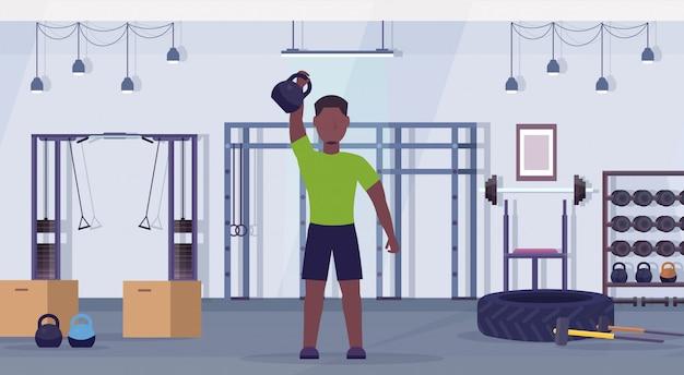 ケトルベルアフリカ系アメリカ人の男がジムの健康的なライフスタイルのコンセプトモダンなヘルスクラブスタジオインテリア水平でトレーニングと演習を行うスポーツ男