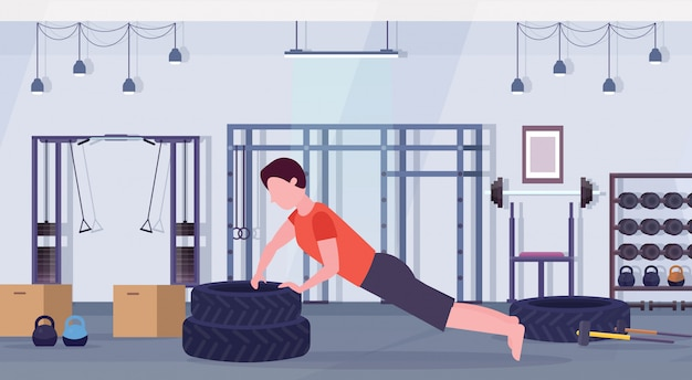 Sports man doing push-up exercise on tires bodybuilder working out in gym hard training healthy lifestyle concept flat modern crossfit healht club interior horizontal