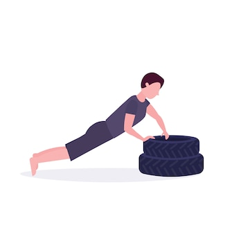 Sports man doing push-up exercise on tires bodybuilder working out in gym hard training healthy lifestyle concept  white background