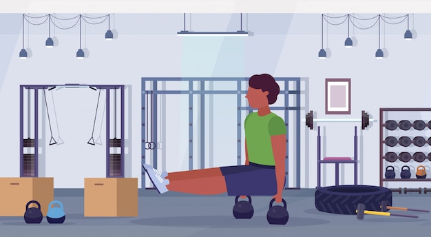 Sports man doing sit-ups exercises with kettlebell african american guy training cardio workout concept modern gym health studio club interior horizontal full length