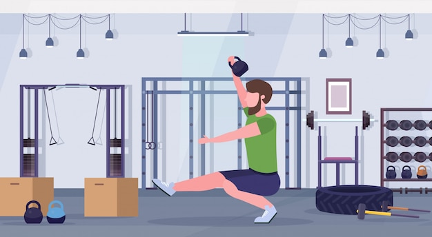 Sports man doing squats exercises with kettlebell guy training cardio workout concept modern gym health studio club interior horizontal full length