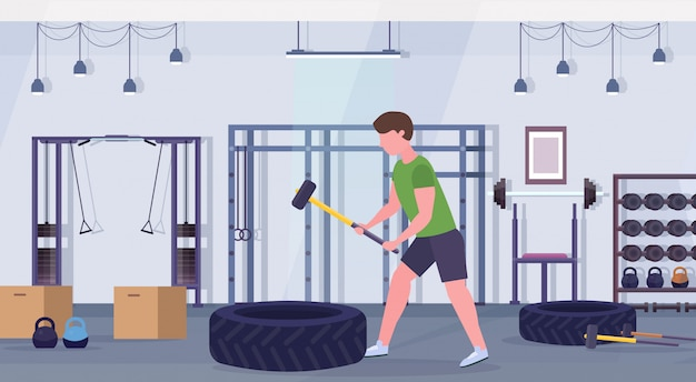 Sports man hitting big tire with hummer doing hard exercises guy working out crossfit training healthy lifestyle concept flat modern gym interior horizontal