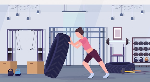 Sports woman flipping a tire doing hard exercises girl working out in gym crossfit training healthy lifestyle concept modern health club studio interior horizontal