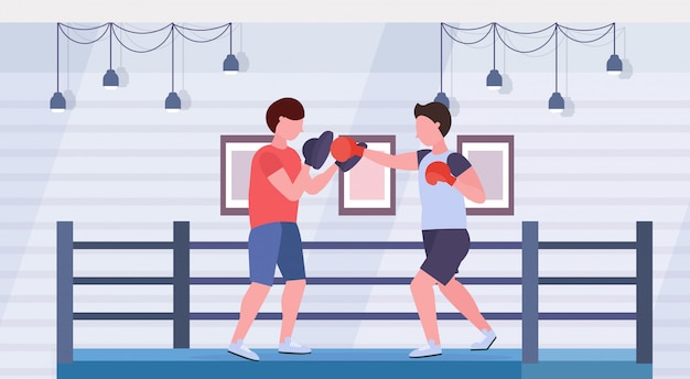 Sportsman boxer practicing boxing exercises with male trainer man fighter in red gloves exercising fight ring arena interior healthy lifestyle concept flat horizontal