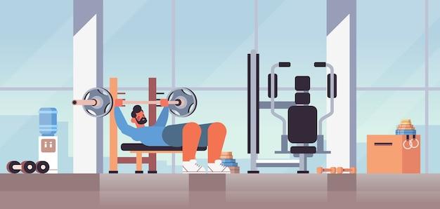 バーベルフィットネストレーニング健康的なライフスタイルのコンセプトモダンなジムのインテリアでベンチプレストレーニングを行うスポーツマン
