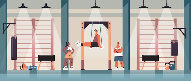 Sportsman gymnast doing abs exercises man exercising on  bar working out fitness training healthy lifestyle concept gym studio interior Premium Vector