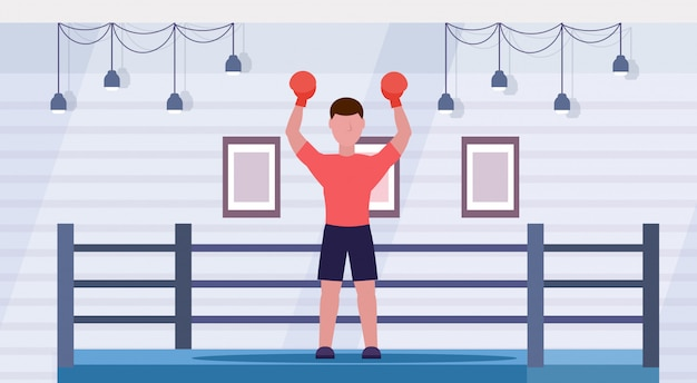 Sportsman in red gloves raised hands professional male boxer celebrating successful fight victory concept boxing ring arena interior horizontal full length