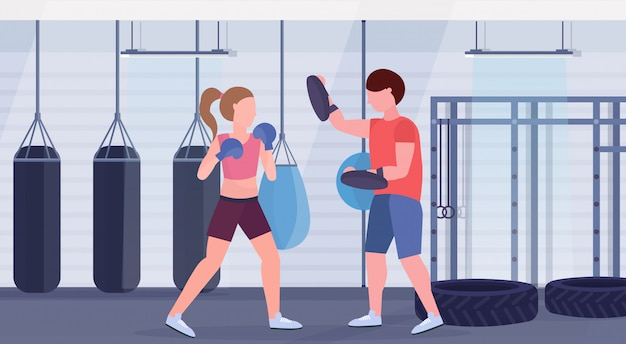 Sportswoman boxer doing boxing exercises with personal trainer girl fighter in blue gloves working out fight club with punching bags gym interior healthy lifestyle concept