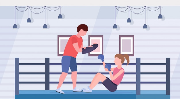Sportswoman boxer doing boxing exercises with personal trainer girl fighter in blue gloves working out on floor fight club ring arena interior healthy lifestyle concept