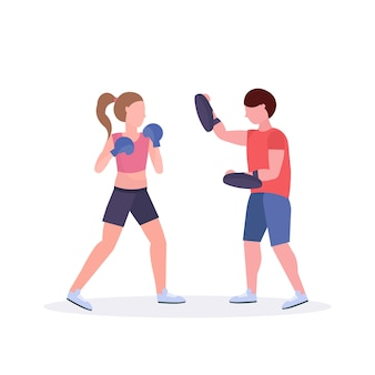 Sportswoman boxer exercising thai boxing with male trainer woman fighter in blue gloves practicing at the fight club healthy lifestyle concept  white background