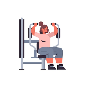 Sportswoman exercising on training apparat girl doing physical exercises working out in gym healthy lifestyle concept