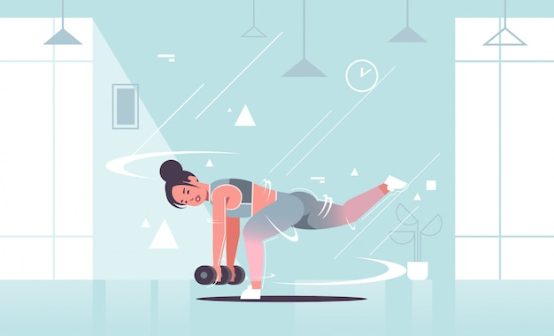 Sporty girl doing stretching exercises with dumbbells