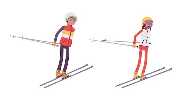 スポーティな男女のスキージャンプ、リゾートでの冬のアウトドアアクティビティ、アクティブな休日、冬の観光、レクリエーションを楽しむ