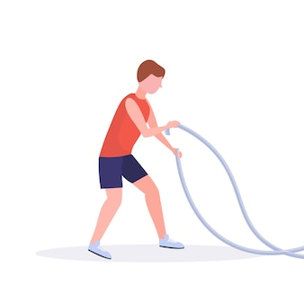 Sporty man doing crossfit exercises with battle rope guy training in gym cardio workout healthy lifestyle concept  white background full length