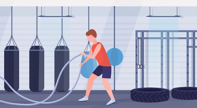 Sporty man doing crossfit exercises with battle rope guy training in gym cardio workout modern boxing fight club studio interior healthy lifestyle concept flat full length horizontal