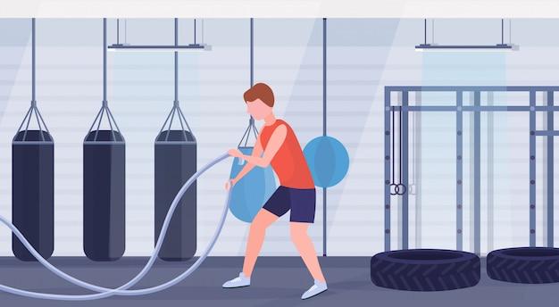 Спортивный человек делает тренировки crossfit с боевой веревкой парень тренировка в тренажерном зале кардио тренировки современный бокс боксерский клуб интерьер здоровый образ жизни концепция плоский полная длина горизонтальный