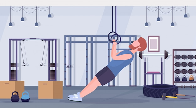 Sporty man doing ring dips exercises with gymnastic rings guy training cardio crossfit workout concept modern gym health club studio interior horizontal full length