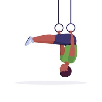 체육관 심장 크로스 핏 운동 건강 한 라이프 스타일 개념 흰색 배경에 전체 길이 체조 링 남자 훈련 링 딥 운동을하는 스포티 한 남자
