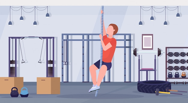 Sporty man doing rope climbing exercise guy training cardio crossfit workout concept modern gym health studio club interior horizontal flat full length