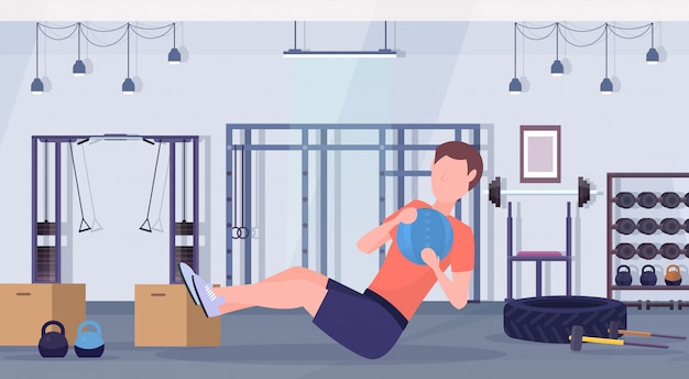 Sporty man doing sit-ups exercises with medicine leather ball guy training cardio workout concept modern gym health studio club interior horizontal full length