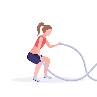 Sporty woman doing crossfit exercises with battle rope girl training in gym cardio workout healthy lifestyle concept  white background full length