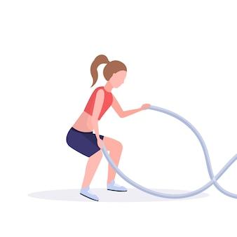 Sporty женщина делая тренировки crossfit с тренировкой девушки веревочки сражения в разминке спортзала кардио концепции здорового образа жизни белизна предпосылки во всю длину