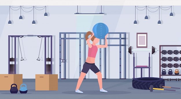 Sporty woman doing crossfit exercises with medicine leather ball girl training cardio workout concept modern gym health studio club interior horizontal full length