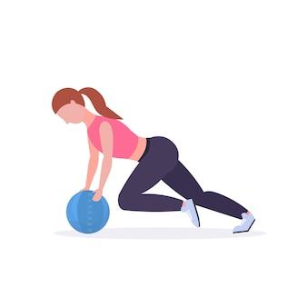 Sporty женщина делая тренировки crossfit с тренировкой девушки кожаного шарика медицины в разминке спортзала кардио концепции здорового образа жизни белая предпосылка во всю длину