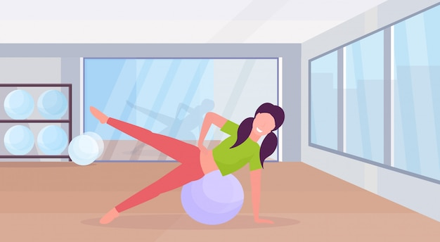 Sporty woman doing exercises with fitness ball girl training in gym aerobic pilates workout healthy lifestyle concept flat modern health club studio interior horizontal