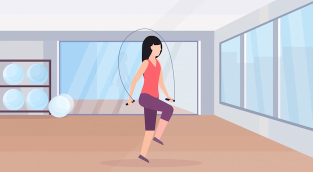 Sporty woman doing exercises with jumping rope girl training in gym aerobic workout healthy lifestyle concept flat modern health club studio interior horizontal