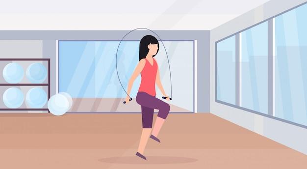Sporty женщина делая тренировки с тренировка скакать веревочки девушка в гимнастике аэробика разминка здоровый образ жизни плоско современно клуб здоровья студия горизонтально