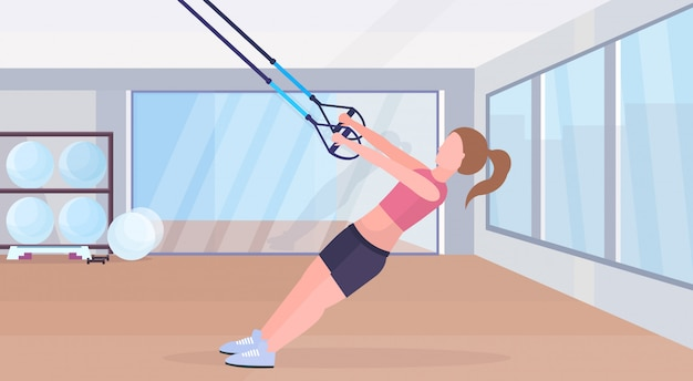 Sporty woman doing exercises with suspension fitness straps elastic rope girl training crossfit workout concept modern gym studio interior horizontal flat full length