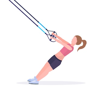Sporty woman doing exercises with suspension fitness straps elastic rope girl training in gym crossfit cardio workout healthy lifestyle concept  white background full length